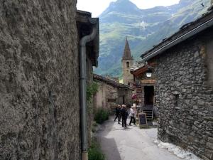 Straatje in Bonneval sur Arc met op de achtergrond het kerkje van het dorp.
