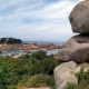 Roze rotsen met daarachter een kasteel op een schiereiland voor de kust bij Ploumanach